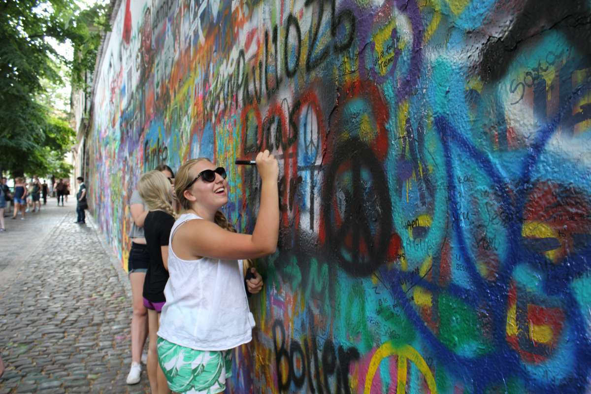 Happy teen travelers sign John Lennon Wall Prague on summer adventure travel program