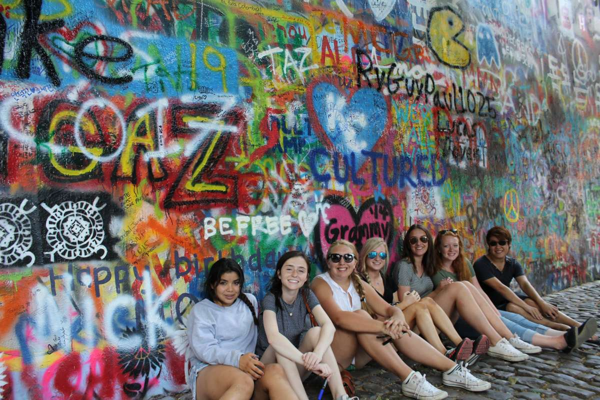 Teenage travelers at John Lennon Wall in Prague on summer teen travel program