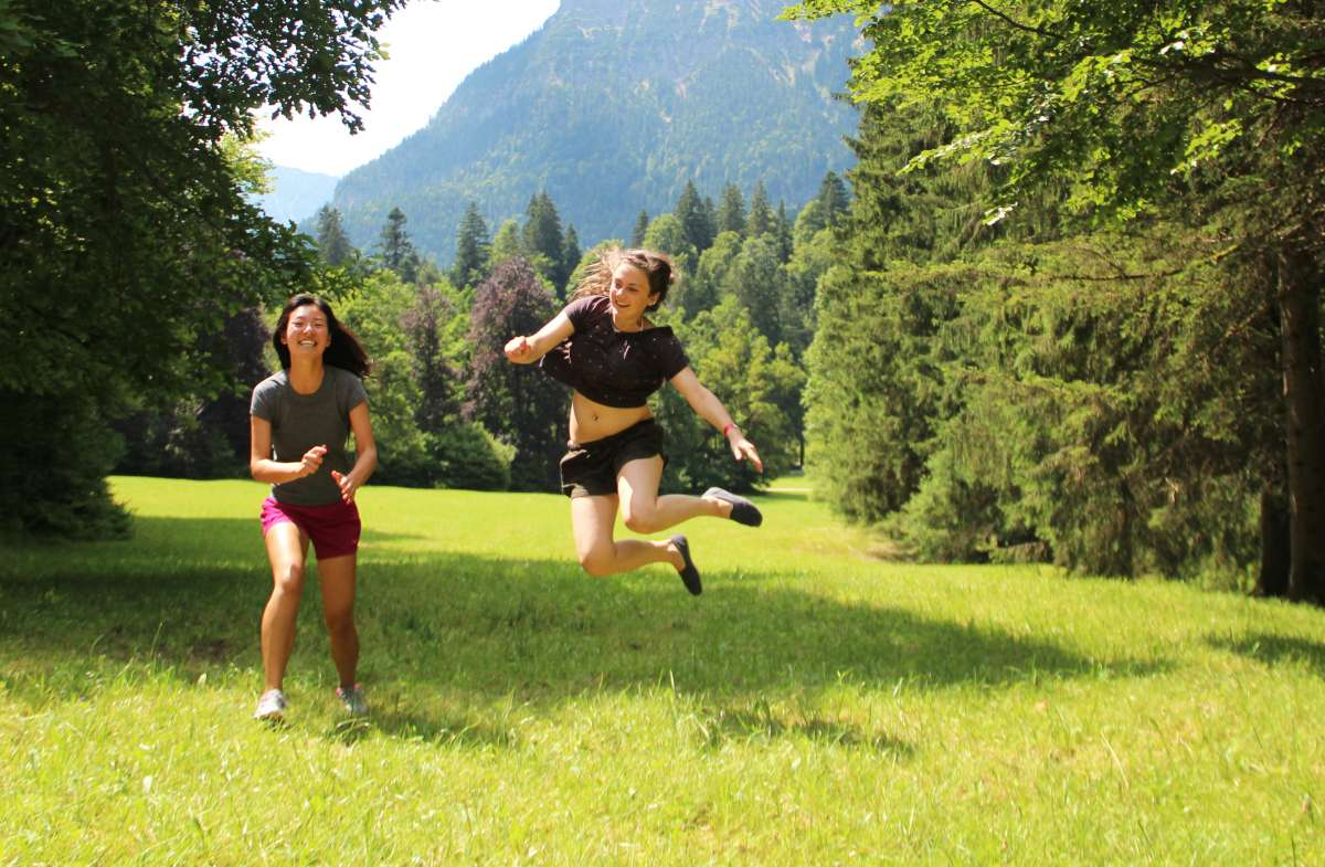 Happy teens explore Swiss Alps on summer youth travel adventure program