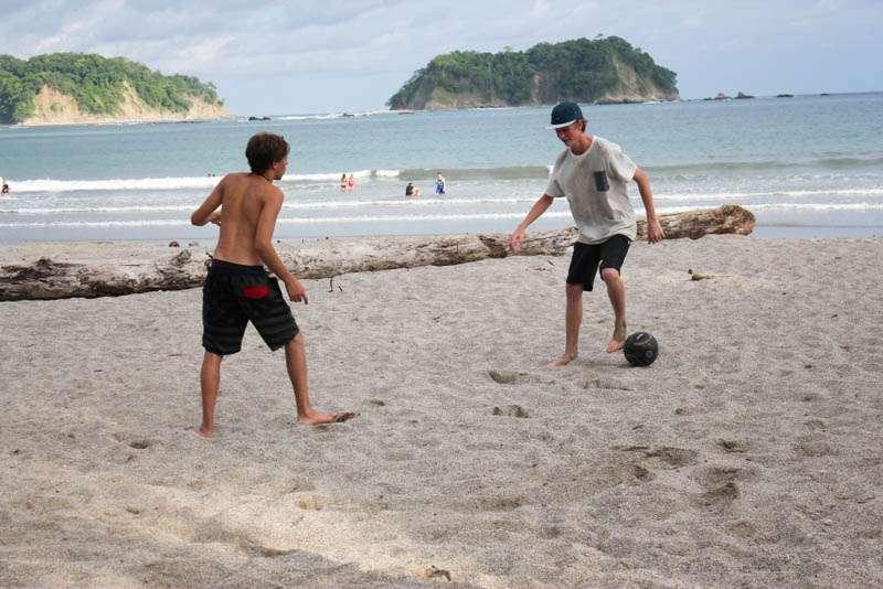 Teen boys play soccer on the beach during their summer travel program in Costa Rica.