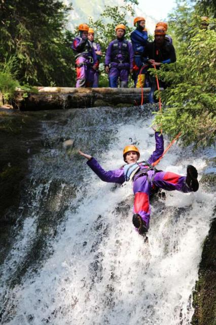 Teens canyoning in Swiss Alps on summer adventure travel program