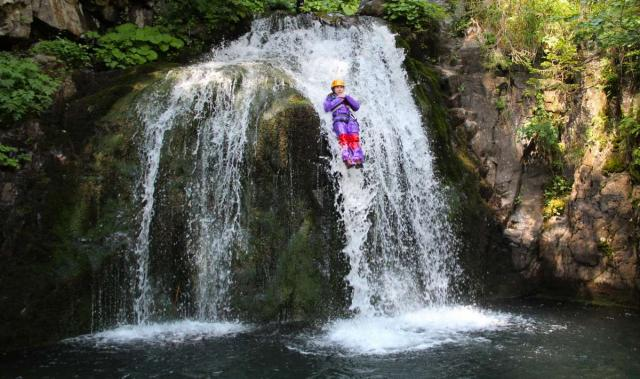 Teen traveler canyoning in Swiss Alps during summer youth adventure program