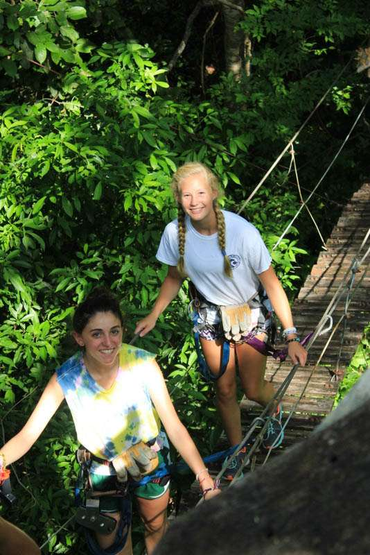 Teens cross rope bridge in the jungles of Costa Rica on summer student adventure program.
