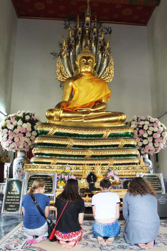 Teenage travelers visit Buddhist temple during summer youth travel program in Thailand