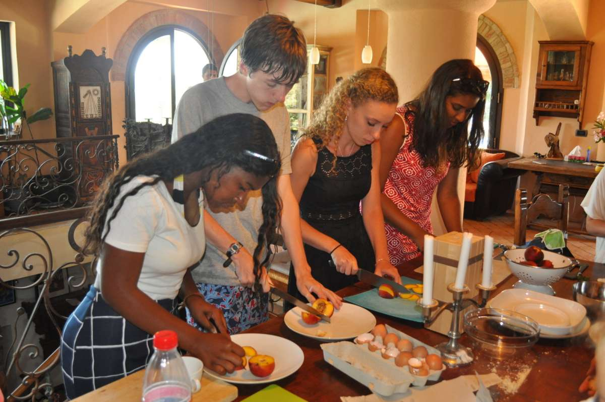 Teenage travelers at Italian cooking class in Tuscan villa on summer youth travel program