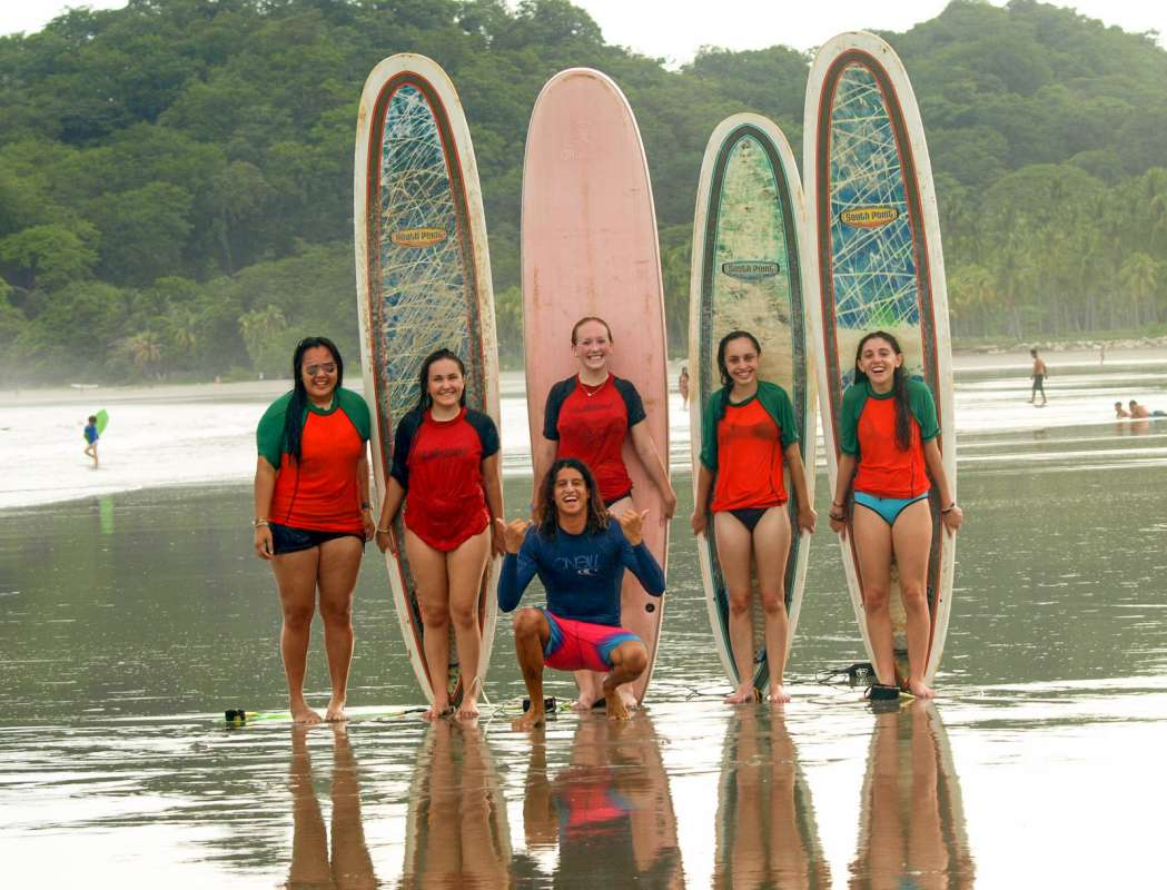 Group of teens go surfing on adventure summer tour in Costa Rica.