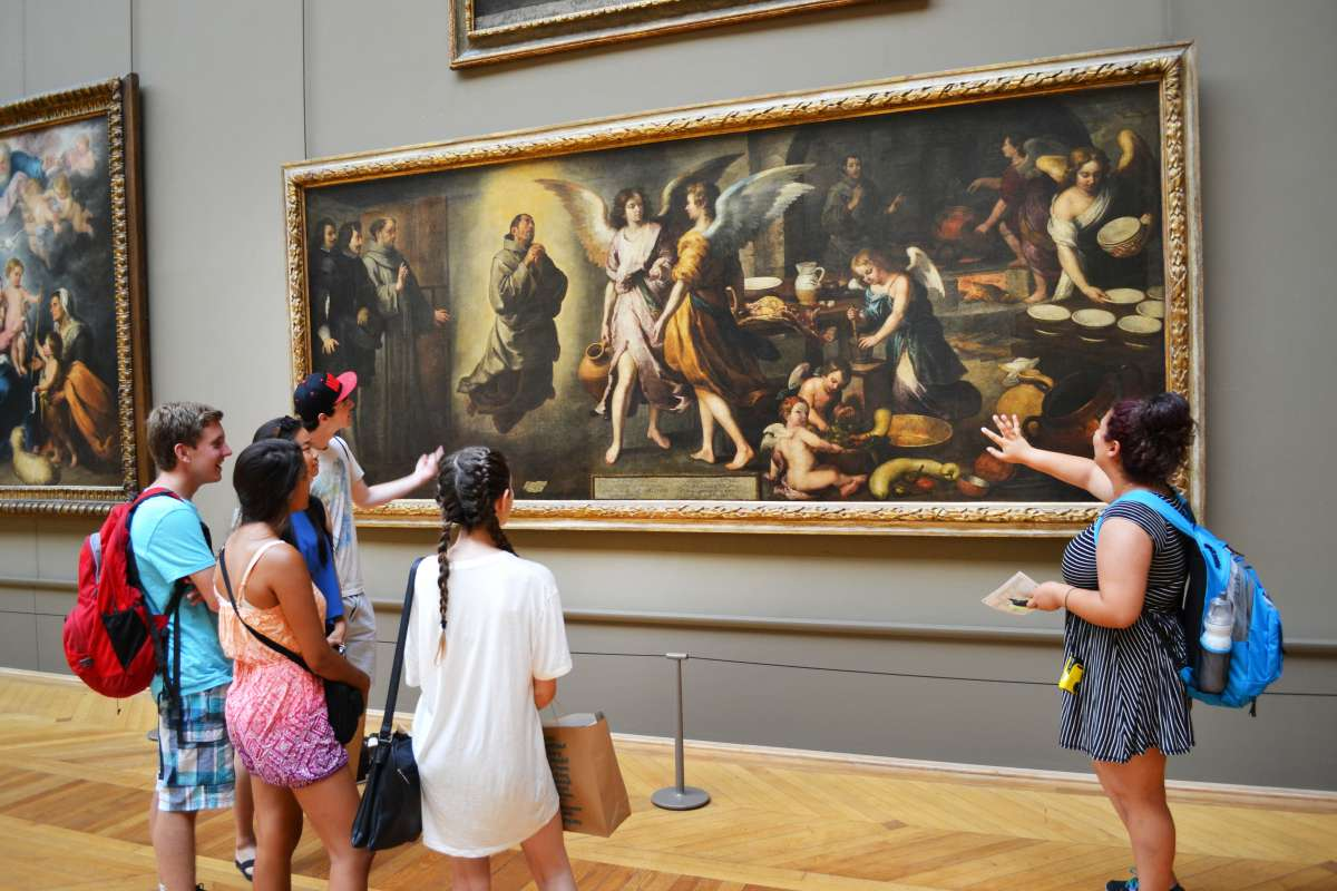 Teen travelers view art during guided tour of Louvre Museum on summer youth travel program