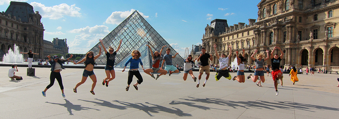 Happy teenage travelers jump at Louvre Museum during summer student travel program
