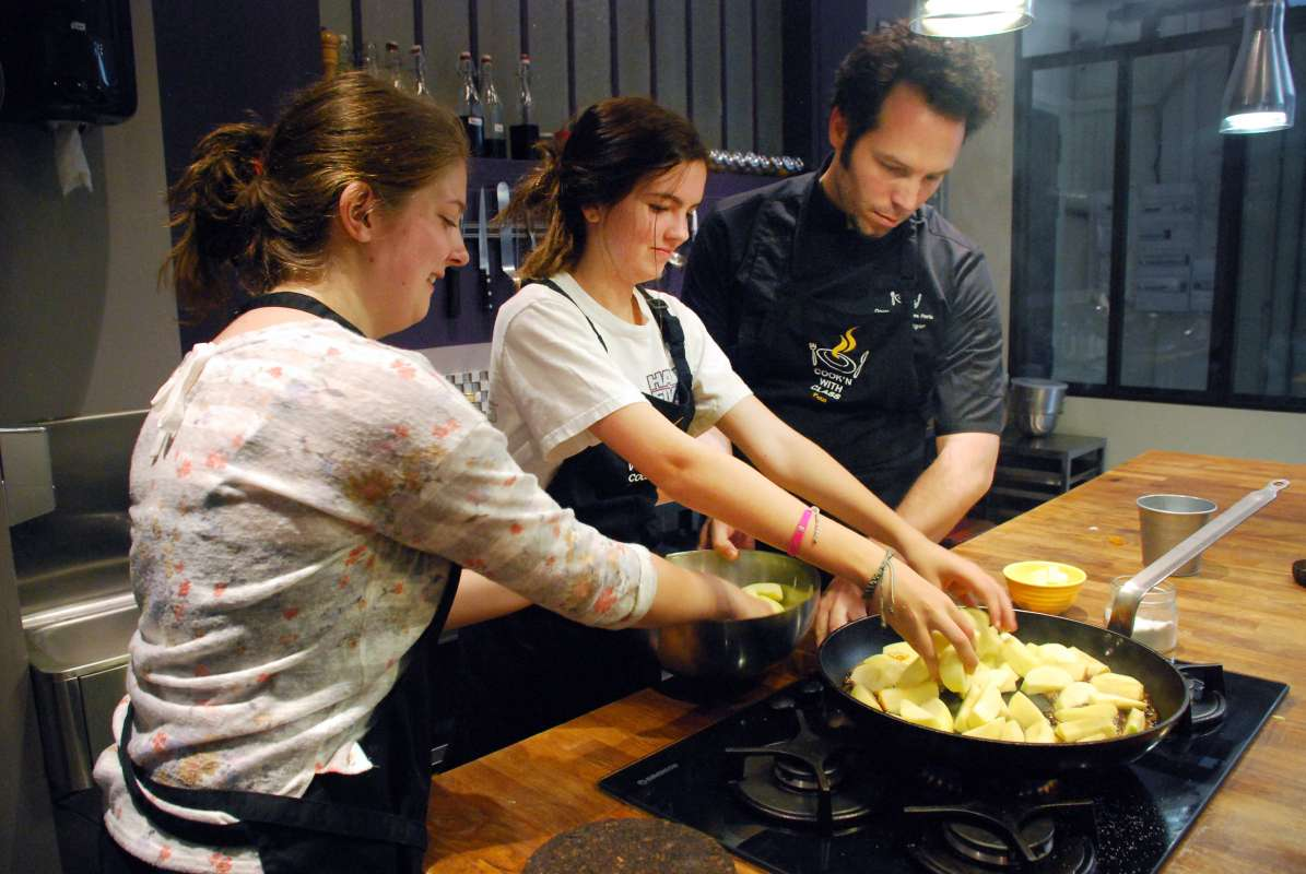 Teenage travelers cook authentic local cuisine in Paris during summer youth travel program