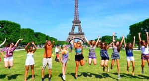 Teenage travelers jumping in front of Eiffel Tower during summer youth program in Paris