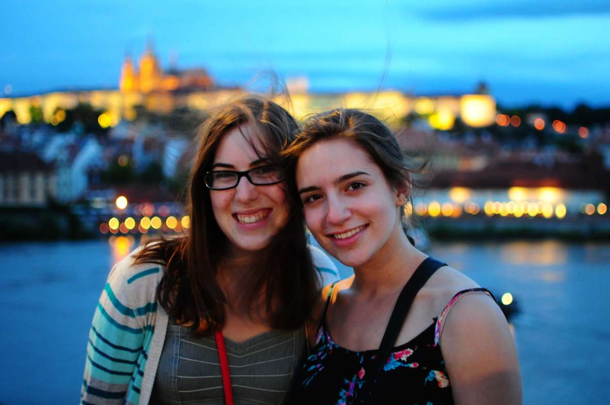 Teen travelers at Vltava River at twilight on summer youth travel program