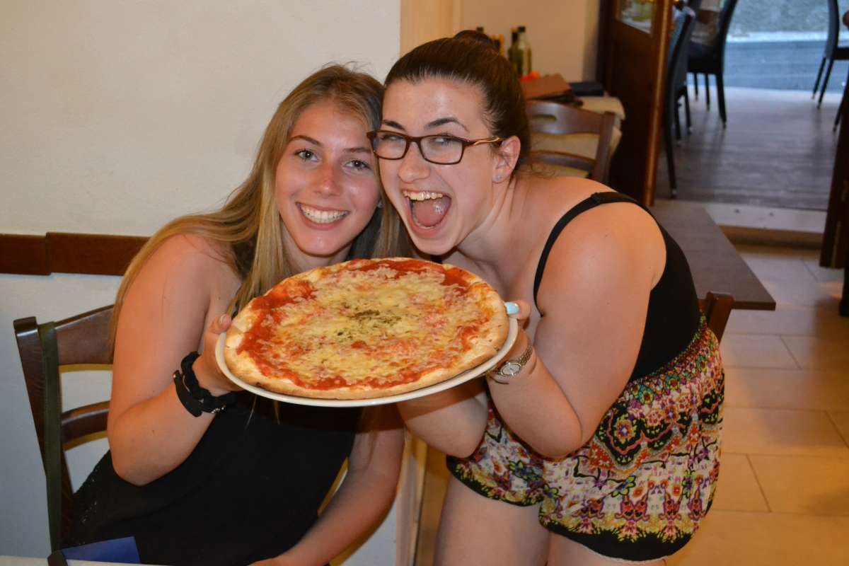 Teen friends pose with authentic pizza on their summer travel program in Italy.