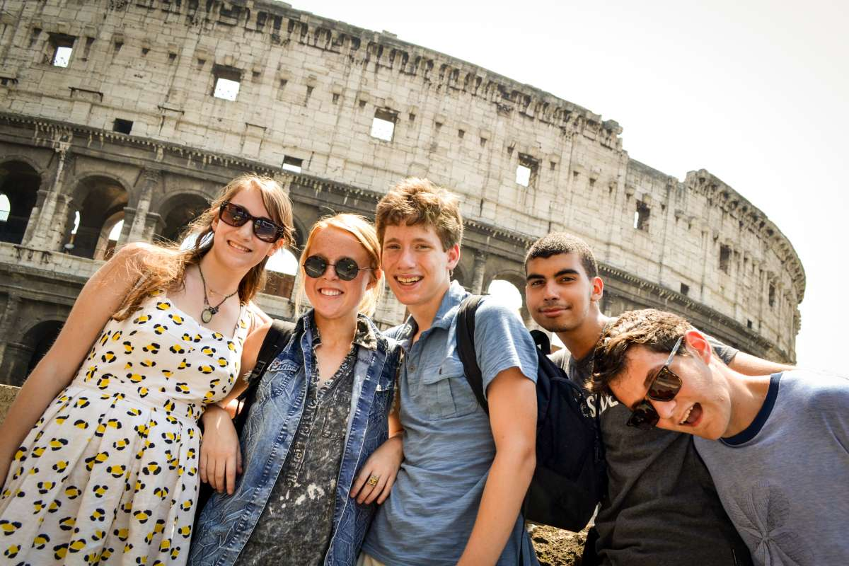 High school students smile outside of the Colosseum on their summer teen tour to Italy.