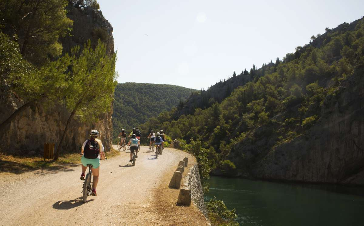Teens bike through Krka Waterfalls on summer youth travel program in Croatia