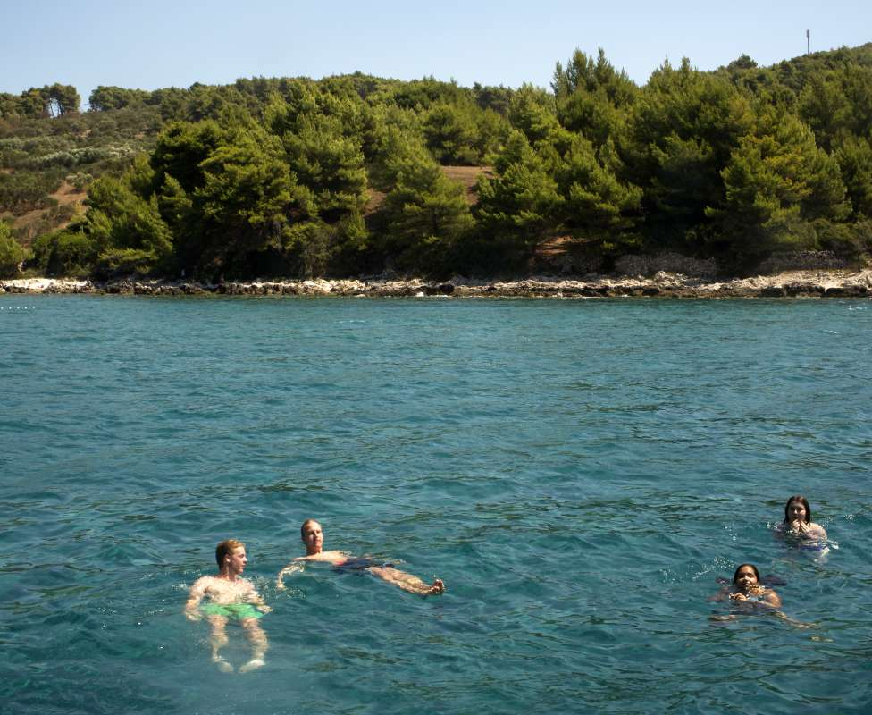 Teens swim in Adriatic Sea on summer travel tour in Croatia