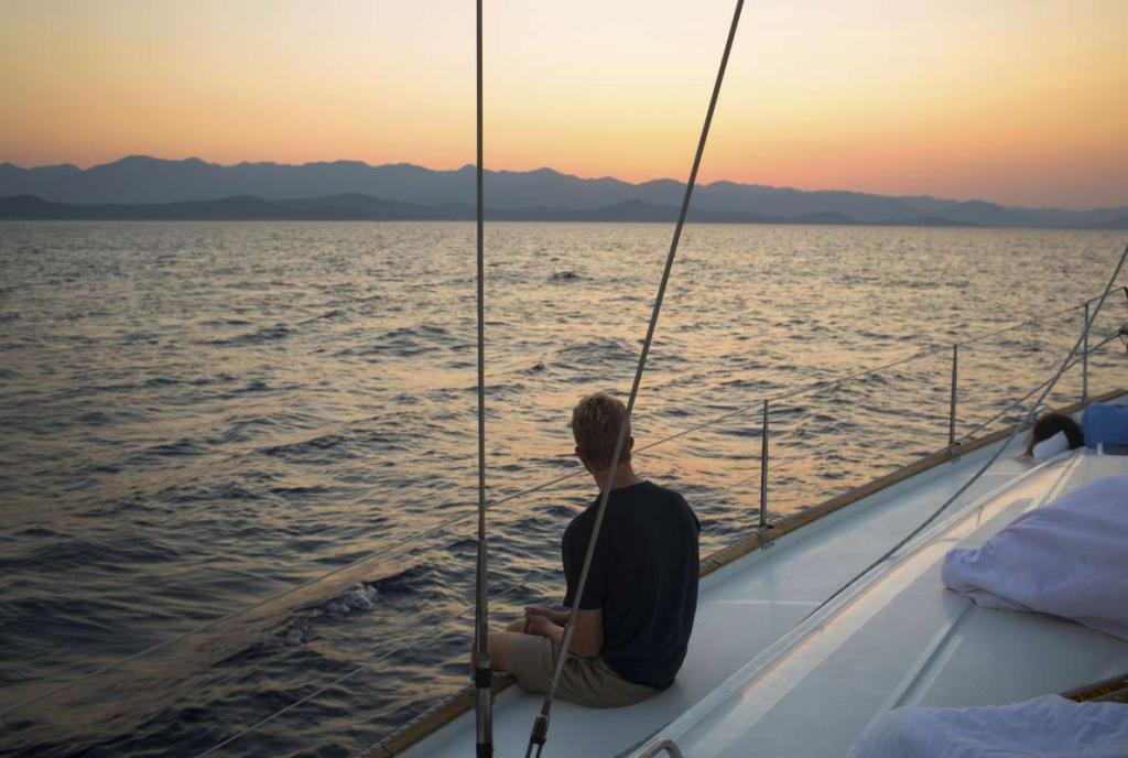 Teen sails through Croatia islands at sunset on summer travel program
