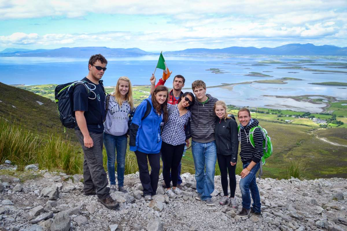 Teen travelers hike Croagh Patrick during summer youth adventure travel program in Ireland