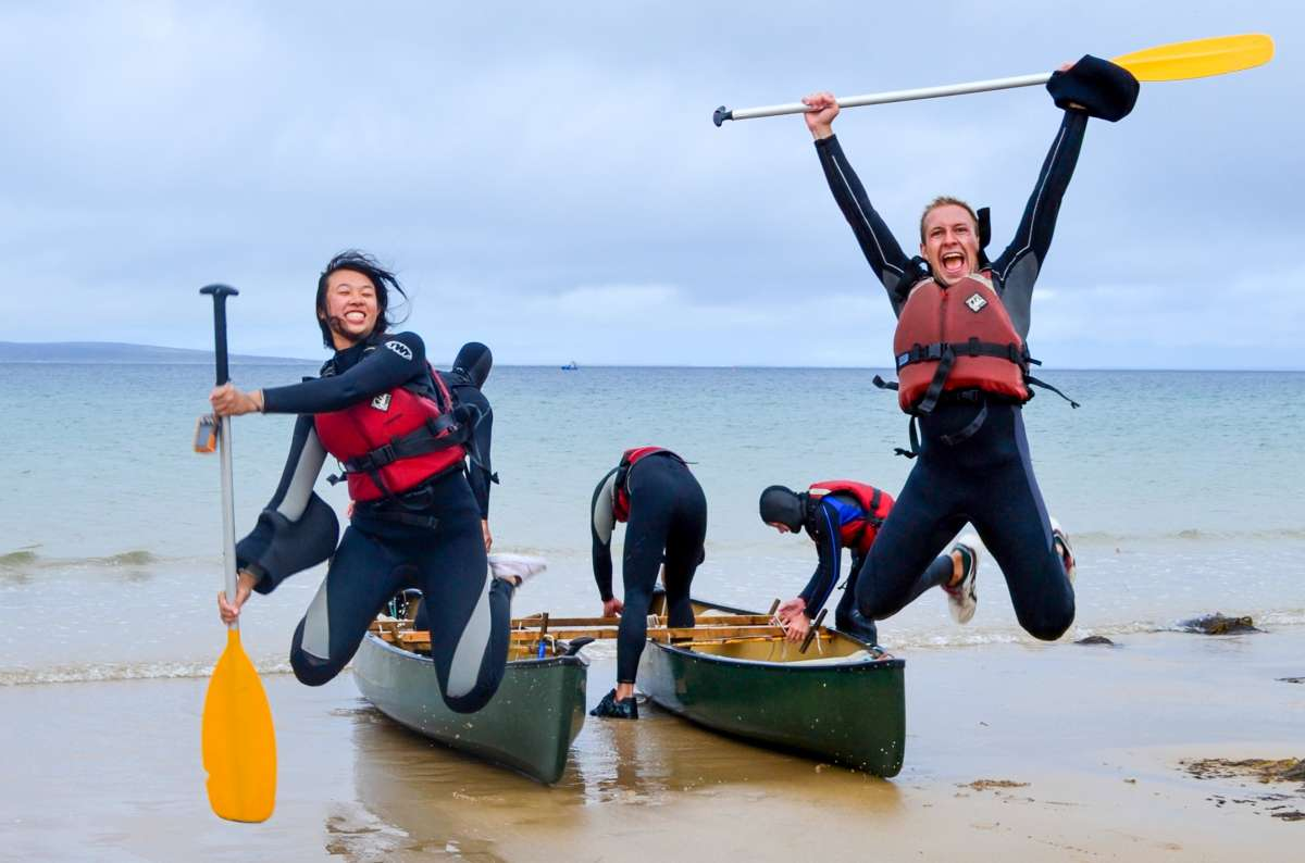 Teen travelers sea canoeing and happy jumping during summer youth adventure travel program in Ireland