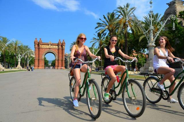 Happy teens biking in Barcelona on Spain summer travel program