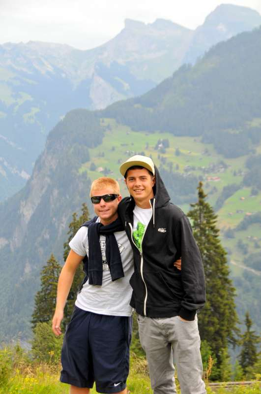 Teenage travelers hiking in Swiss Alps during summer teen adventure travel program