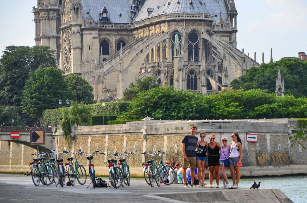 Teenage travelers bike by Notre Dame Cathedral and River Seine on summer youth travel program in Paris