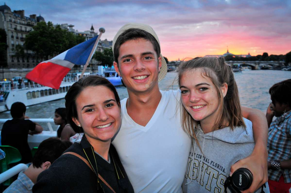 Teenage travelers cruise down Seine at sunset during summer youth travel program in Paris