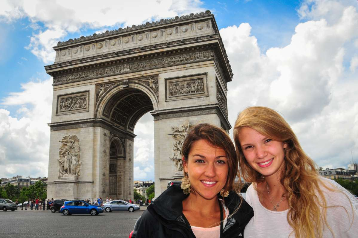 Smiling teenage travelers visit Arc de Triomphe during summer student travel program in France