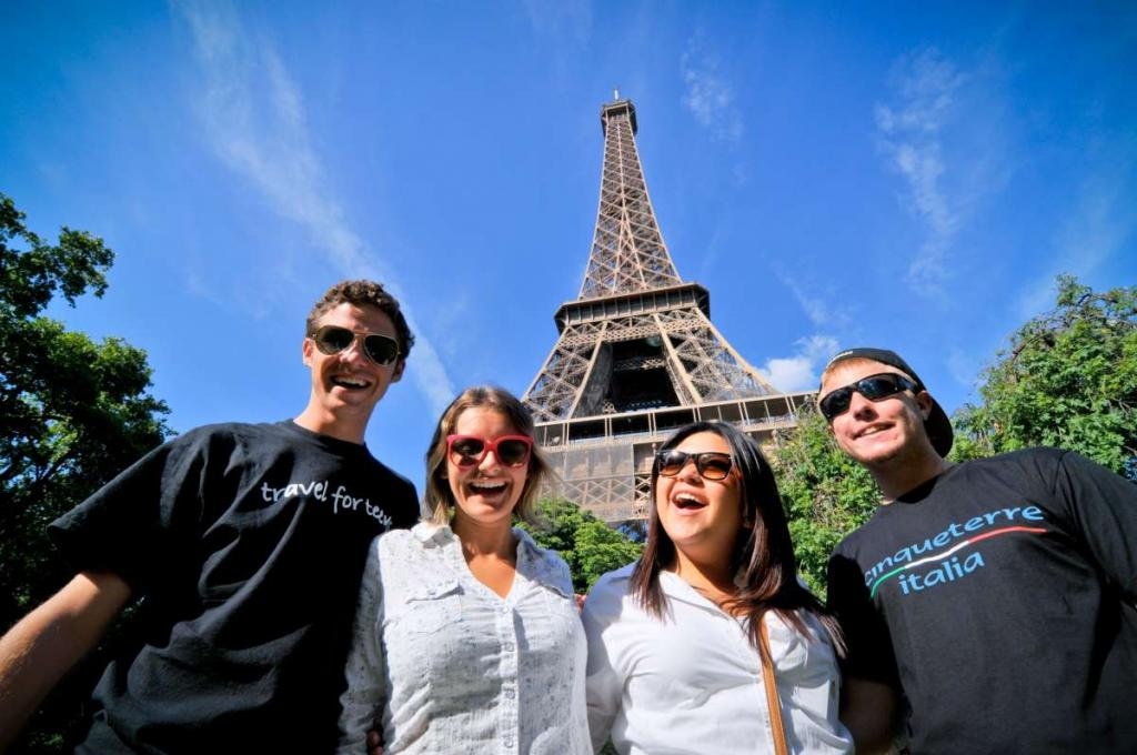 Happy laughing teenage travelers visit Eiffel Tower on summer student program in France