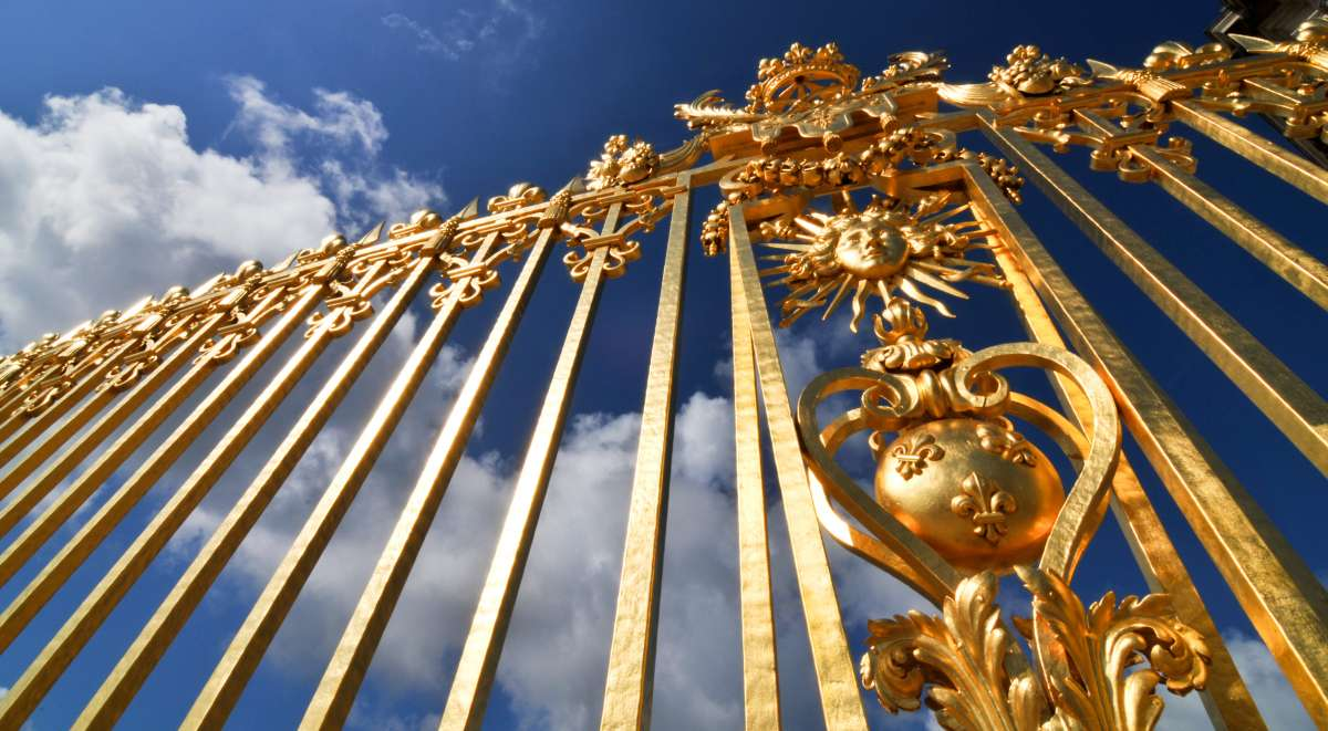 Golden gates of Chateau de Versailles visited by teen travelers on French language immersion program in Paris