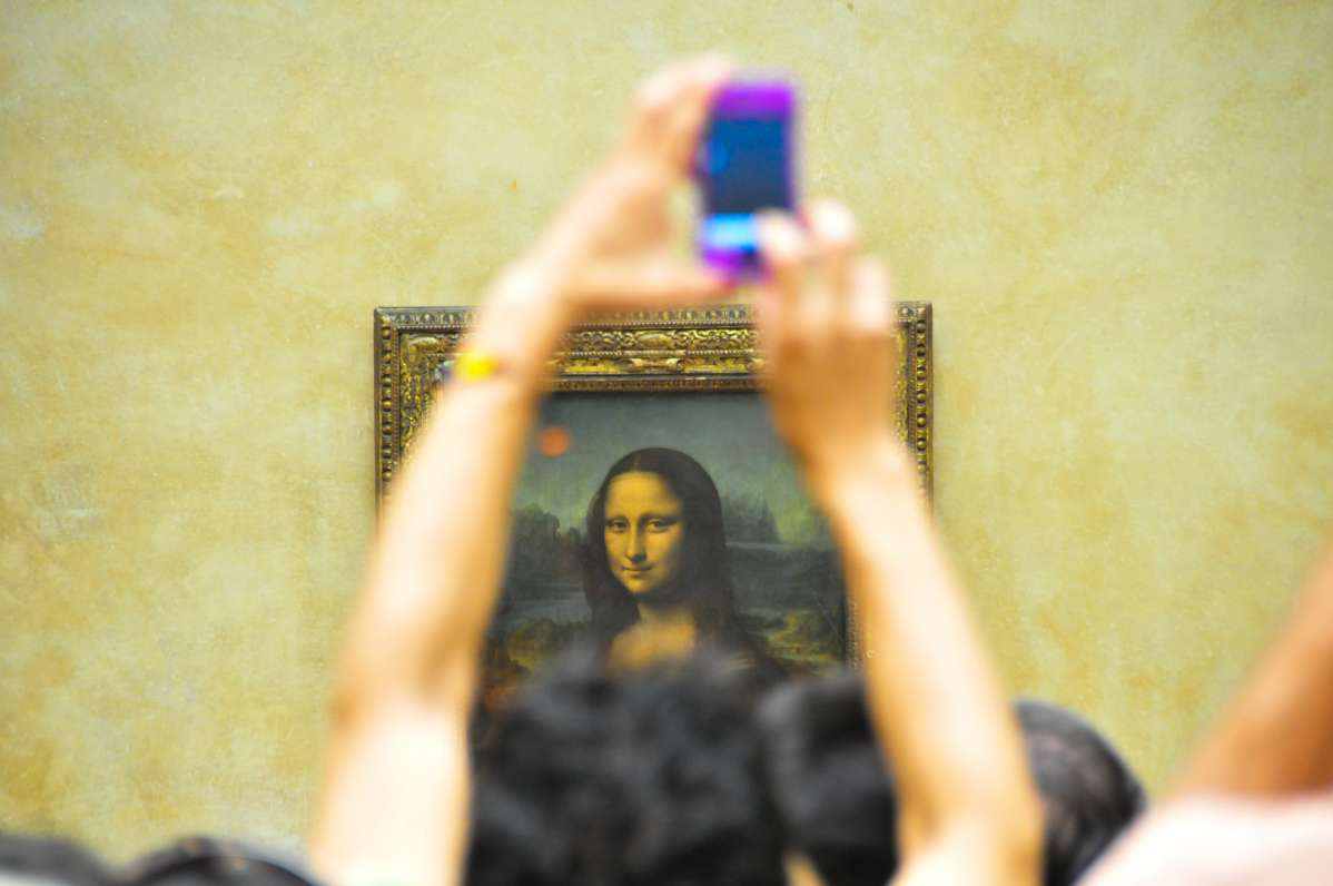 Teenage traveler photographing Mona Lisa at Louvre Museum in Paris during summer French language immersion program