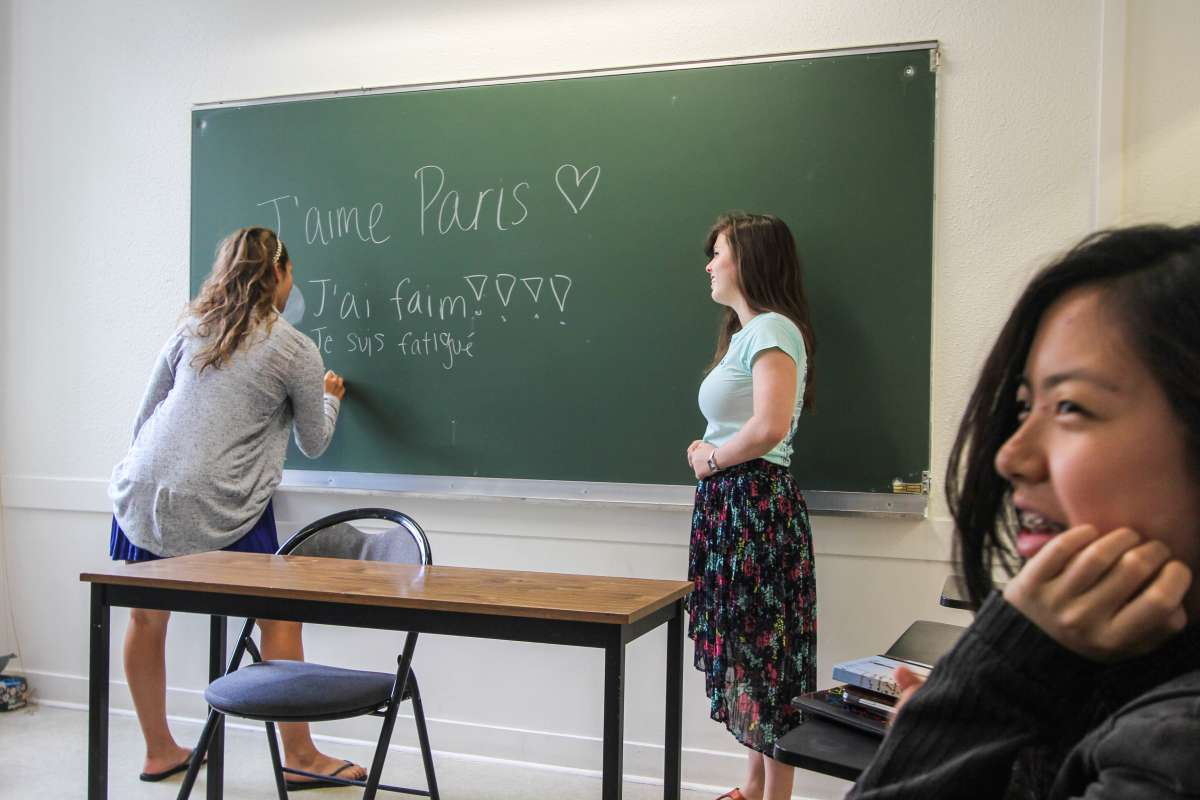 Teenage traveler writing in French at language school during summer travel immersion program in Paris