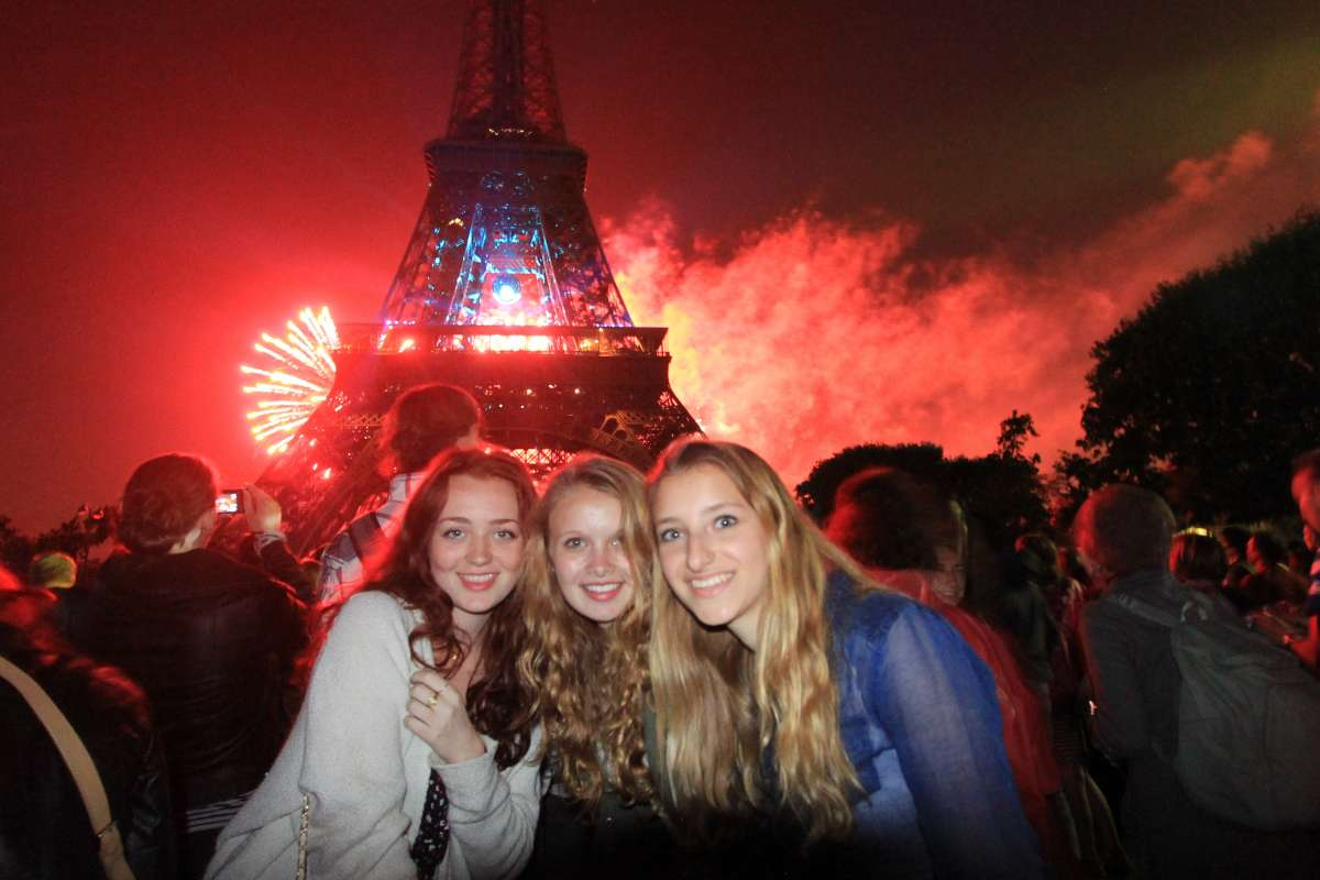 Teenage travelers watch fireworks on Champs de Mars at Eiffel Tower during summer travel adventure program