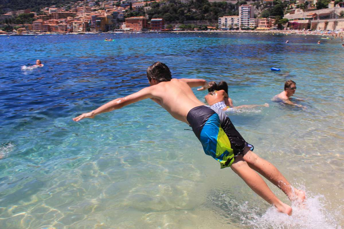 Teenage boy jumps into Mediterranean Sea during summer France language immersion program in French Riviera