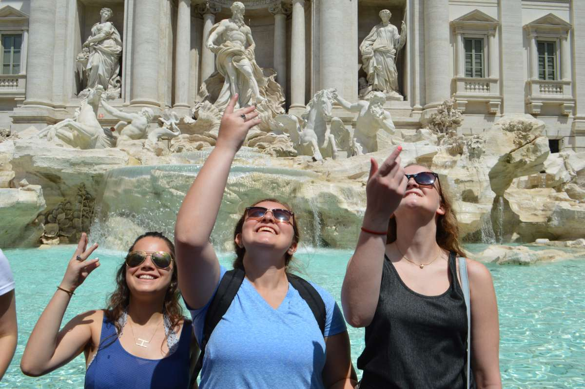 Happy teen travelers toss coin in Trevi Fountain Rome during summer youth program in Italy