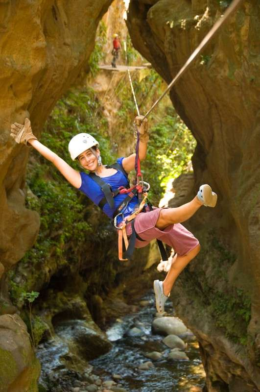 Teens go zip-lining through canyon in Costa Rica on adventure summer program.