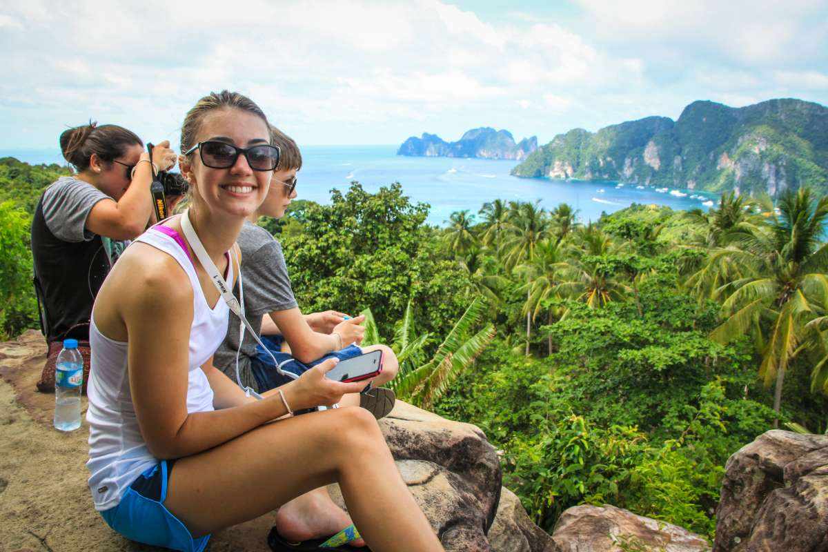 Teenage travelers hiking and resting with beautiful views during summer youth travel program in Thailand