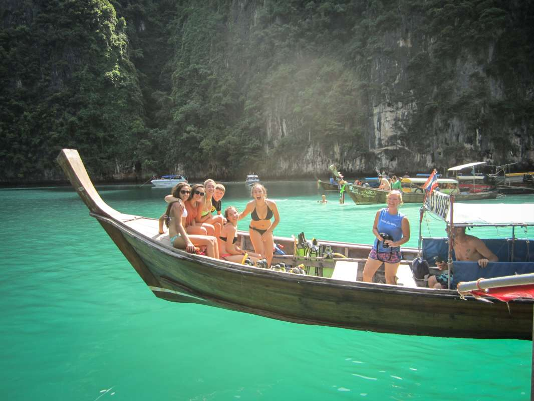 Teenage travelers on traditional boat cruise during summer youth travel program in Thailand