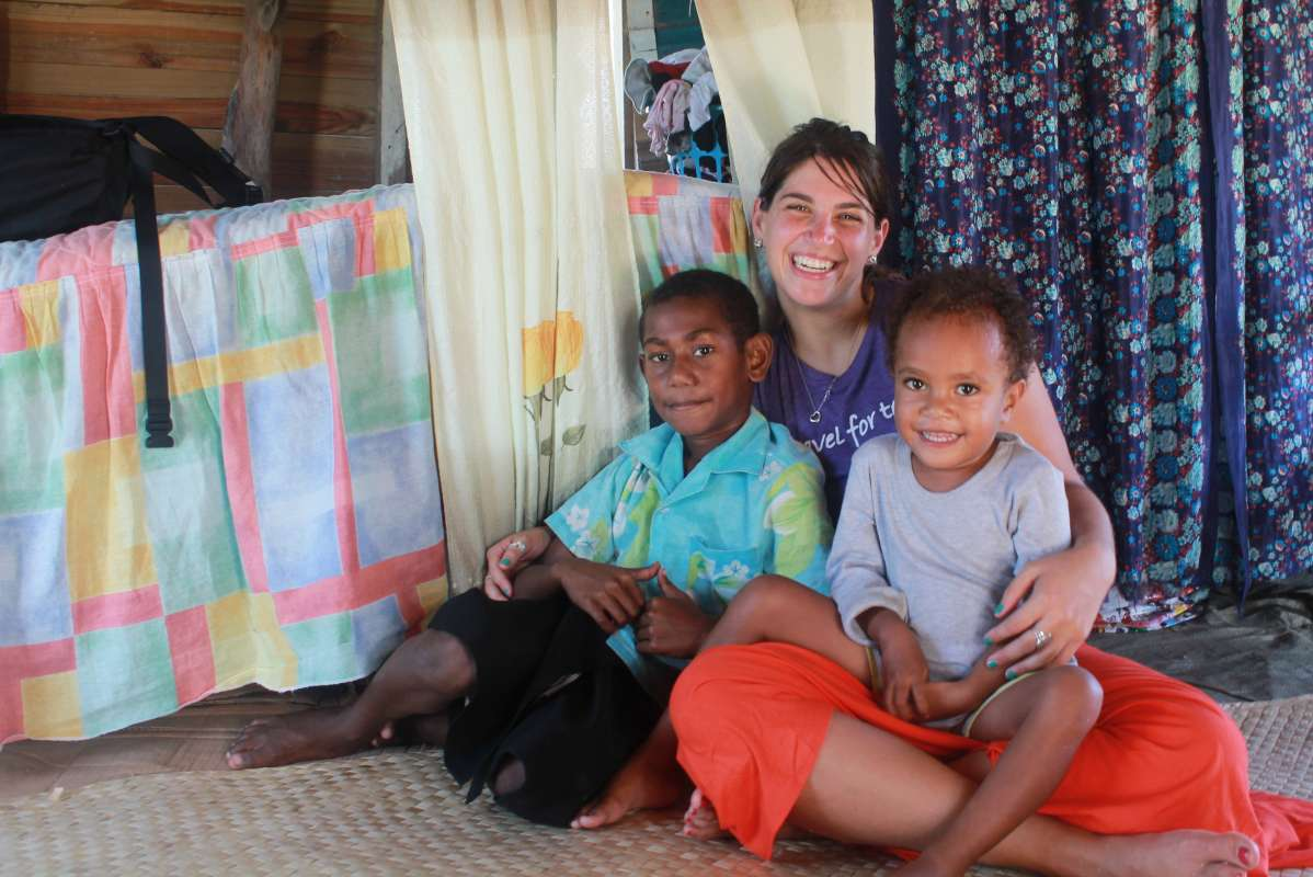 Teen traveler with local children during summer youth program in Fiji