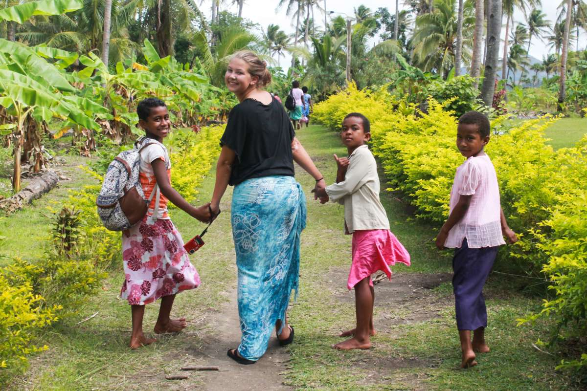 Happy teenage traveler walks with local children during summer youth program in Fiji
