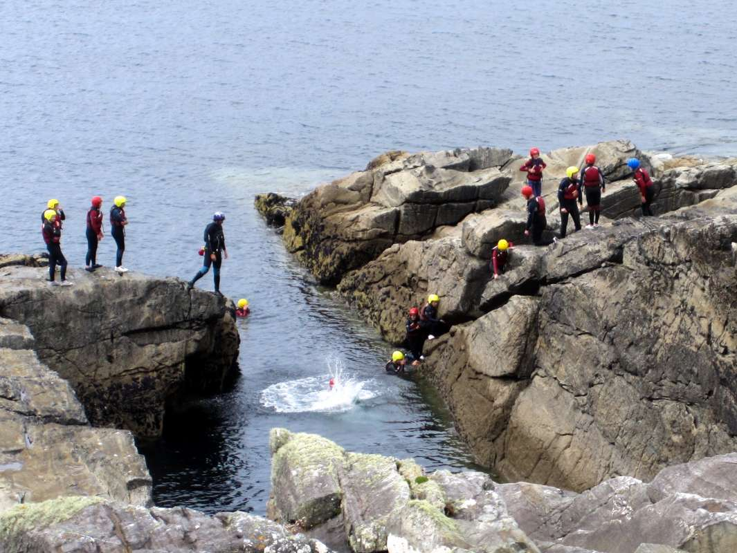 Teen travelers coasteering during summer youth adventure travel program in Ireland