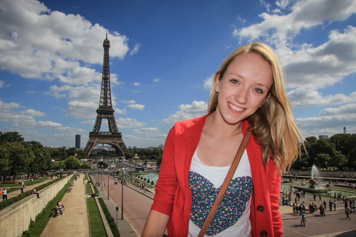 Teen traveler with Eiffel Tower in Paris during summer youth travel program