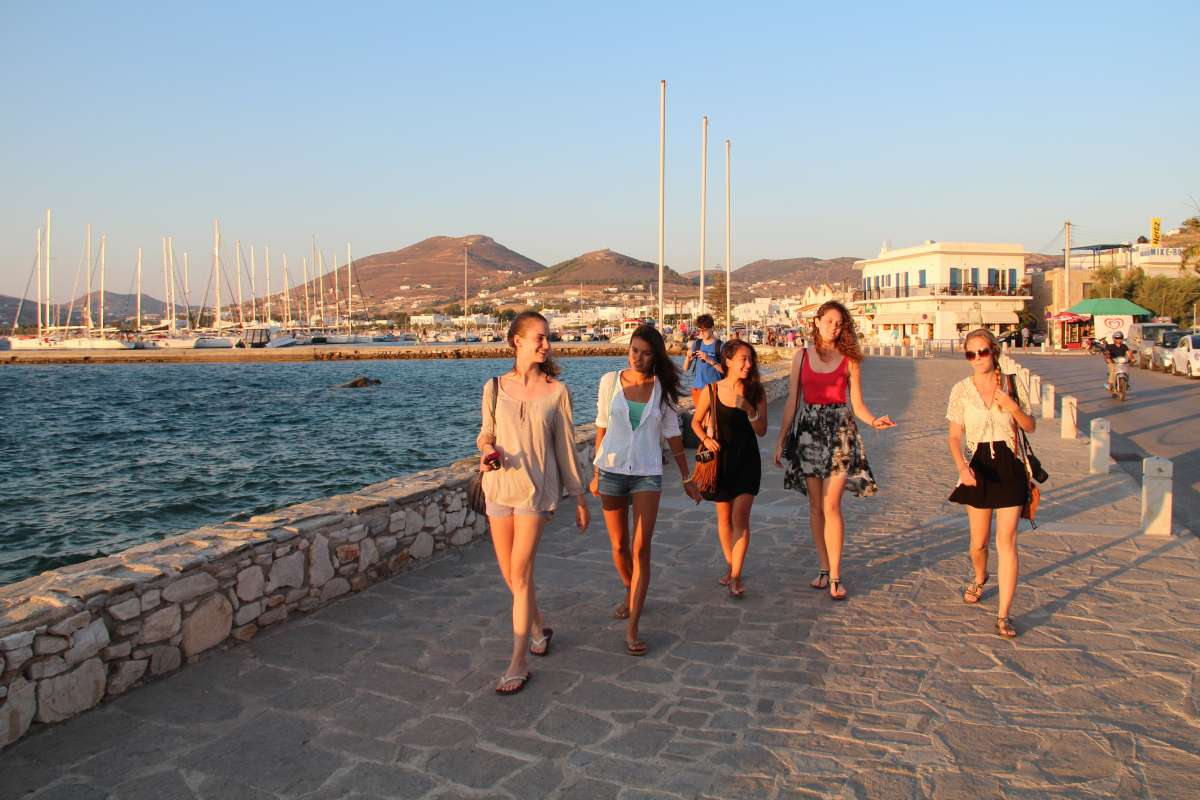Teenage travelers walk along port boardwalk during summer youth travel program in Greece