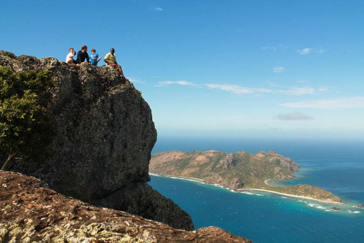 Teen travelers sit atop high rock and enjoy breathtaking views during summer youth program in Fiji