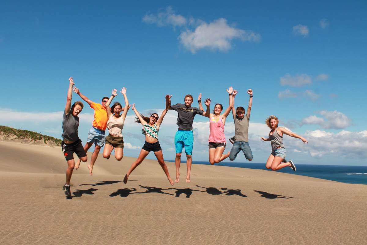 Happy teen travelers jump on sand dunes during summer youth program in Fiji