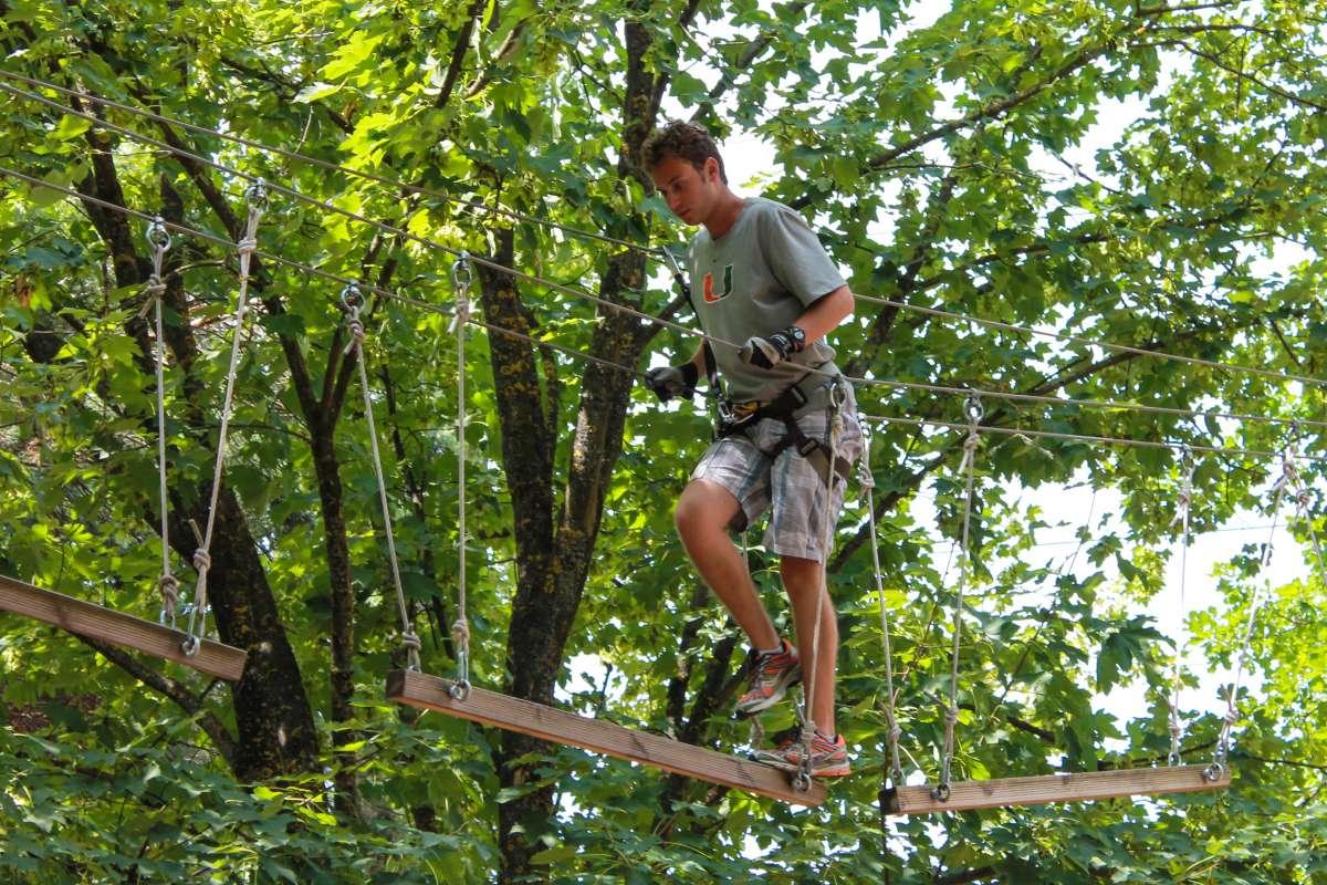 Teen traveler doing ropes course in Switzerland during summer adventure travel program