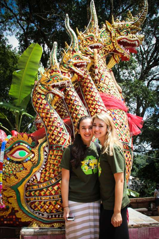 Teenage travelers pose with dragon statues during summer youth travel program in Thailand