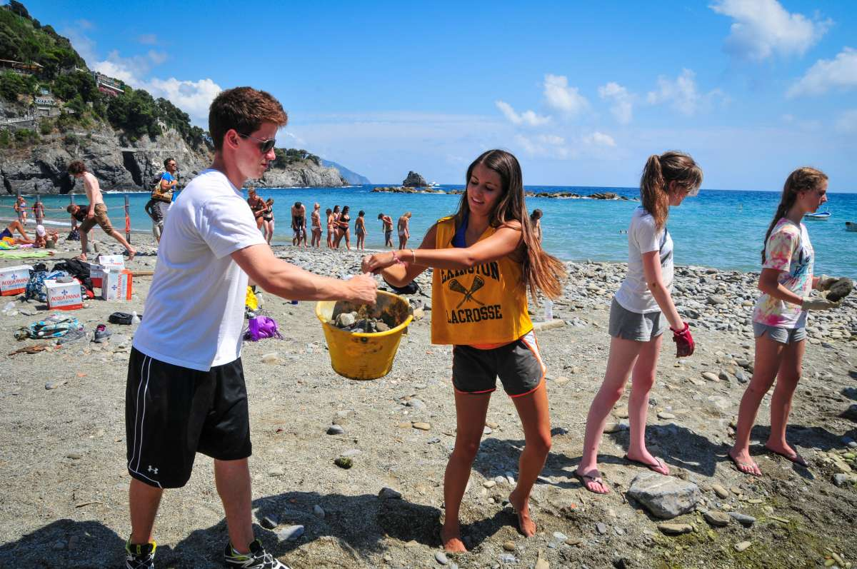 High school students complete service hours on a beach in the Cinque Terre on their summer teen tour to Italy.