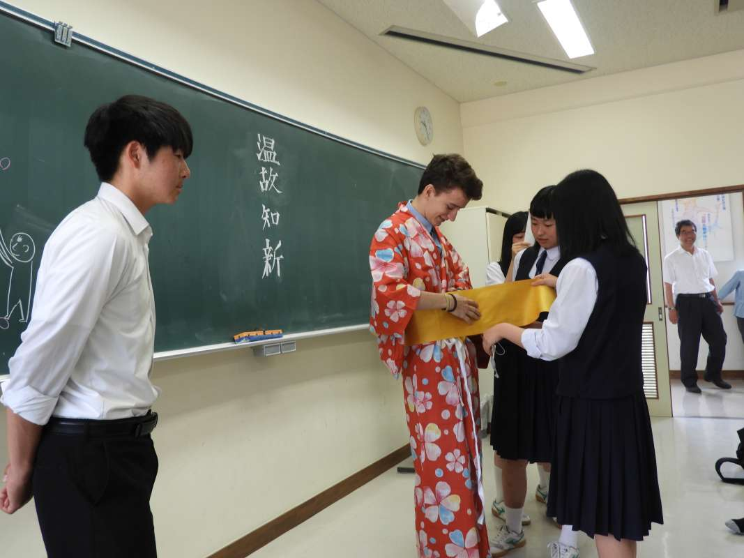 Japanese students teach American student how to put on traditional kimono during summer youth travel program in Japan