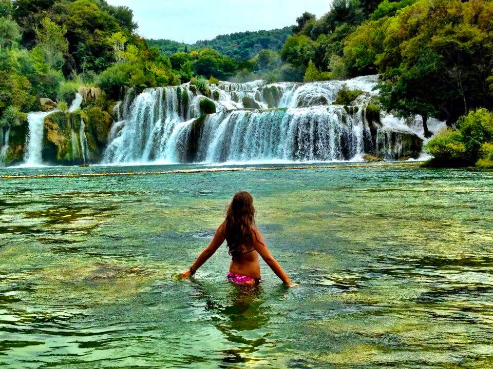 Teen travelers swim in Krka Waterfalls on summer youth travel program