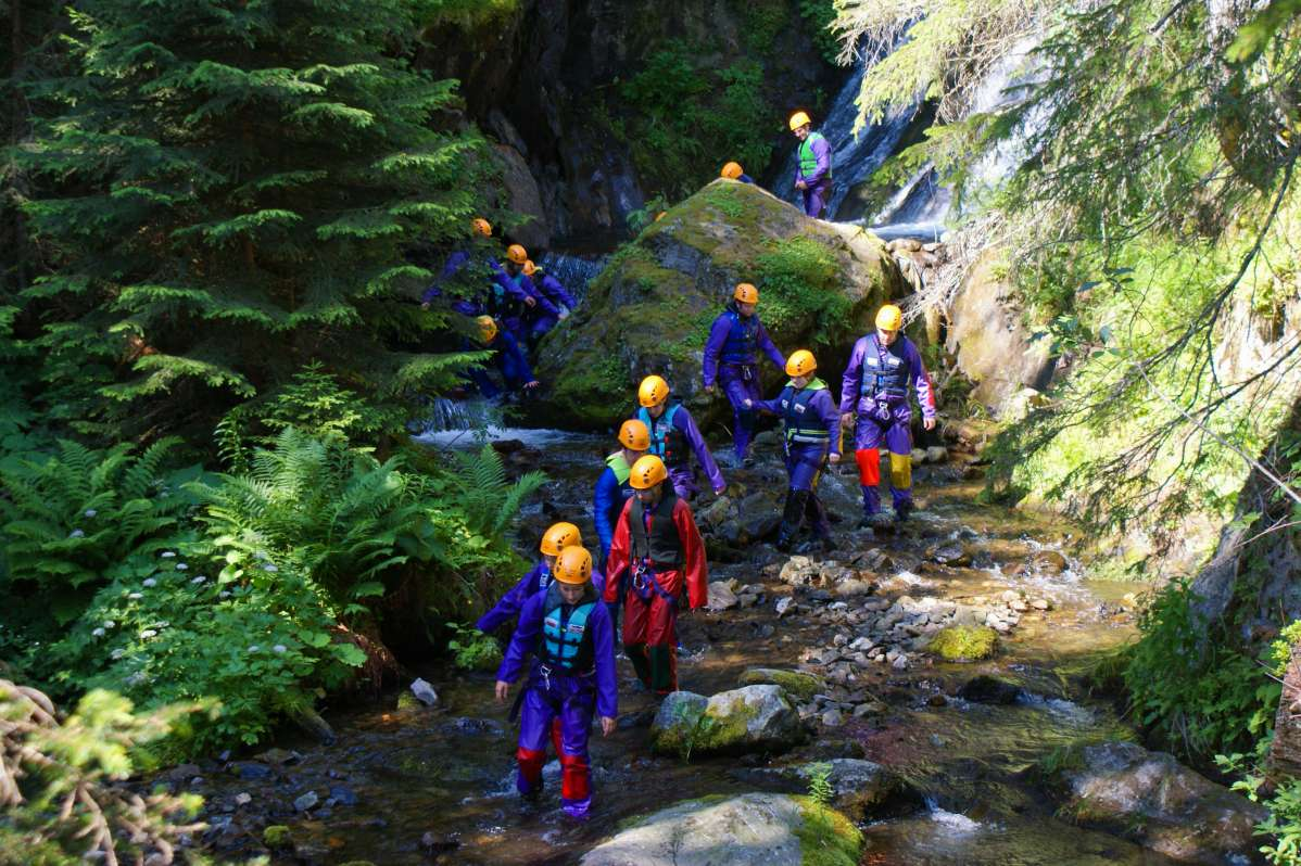 Teenage travelers canyoning on European summer adventure tour
